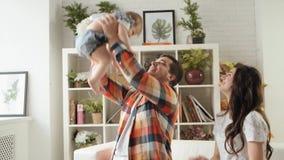 Ο νέος ευτυχής πατέρας ρίχνει επάνω στην κόρη μωρών του που παίζει με την παράλληλα με τη μητέρα της σε αργή κίνηση απόθεμα βίντεο
