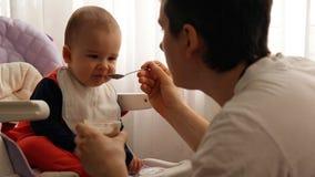 Ο νέος ευτυχής πατέρας ταΐζει το κουάκερ μωρών γιων του απόθεμα βίντεο