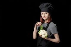 Ο νέος ελκυστικός αρχιμάγειρας γυναικών μαύρο σε ομοιόμορφο κρατά το φρέσκο κουνουπίδι στο μαύρο υπόβαθρο Στοκ εικόνες με δικαίωμα ελεύθερης χρήσης