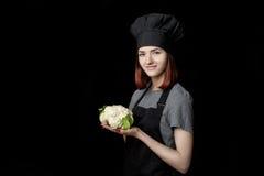 Ο νέος ελκυστικός αρχιμάγειρας γυναικών μαύρο σε ομοιόμορφο κρατά το φρέσκο κουνουπίδι στο μαύρο υπόβαθρο Στοκ φωτογραφίες με δικαίωμα ελεύθερης χρήσης
