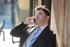 Ο νέος ελκυστικός και πολυάσχολος επιχειρηματίας με τη φθορά μπλε ματιών ταιριάζουν και η ομιλούσα επιχείρηση δεσμών στο κινητό τ Στοκ Εικόνες
