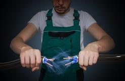 Ο νέος ηλεκτρολόγος κρατά τα καλώδια στα χέρια και τη σύνδεση τους Αστραπή και ηλεκτρική ενέργεια γύρω Στοκ Φωτογραφίες