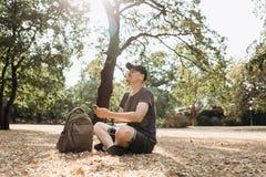 Ο νέος θετικός τύπος ή ο σπουδαστής με ένα σακίδιο πλάτης κάθεται και ακούει τη μουσική στοκ εικόνα