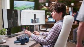 Ο νέος θηλυκός αρχιτέκτονας χρησιμοποιεί ένα CAD ή ένα τρισδιάστατο λογισμικό για να σχεδιάσει ένα νέο κτήριο απόθεμα βίντεο