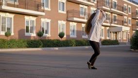 Ο νέος θηλυκός εκτελεστής χορού χορεύει σε ένα ναυπηγείο μπροστά από τα σύγχρονα σπίτια διαβίωσης σε μια πόλη το θερινό βράδυ φιλμ μικρού μήκους