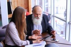 Ο νέος θηλυκός προϊστάμενος υποστηρίζει ότι ο παλαιός υπάλληλος συζητά τα προβλήματα στην επιχείρηση Στοκ εικόνα με δικαίωμα ελεύθερης χρήσης