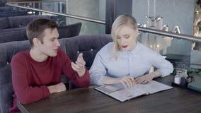 Ο νέος θηλυκός σχεδιαστής συζητά το πρόγραμμα με τον αρσενικό πελάτη στο άνετο εστιατόριο, σε αργή κίνηση φιλμ μικρού μήκους