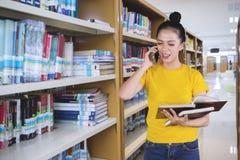 Ο νέος θηλυκός φοιτητής πανεπιστημίου κάνει ένα τηλεφώνημα στοκ εικόνα με δικαίωμα ελεύθερης χρήσης