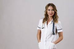 Ο νέος θηλυκός γιατρός φορά ένα άσπρο παλτό γιατρών ` s με ένα στηθοσκόπιο Στοκ εικόνες με δικαίωμα ελεύθερης χρήσης