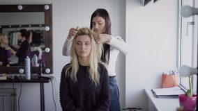 Ο νέος θηλυκός κομμωτής του σαλονιού ομορφιάς πολυτέλειας στέκεται και εργάζεται με το νέο ξανθό πρότυπο με το σίδηρό της όμορφος απόθεμα βίντεο