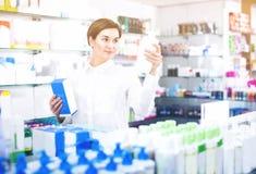 Ο νέος θηλυκός πελάτης κοιτάζει βιαστικά τις σειρές των προϊόντων προσοχής σωμάτων Στοκ Εικόνα