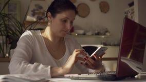 Ο νέος θηλυκός σχεδιαστής εξετάζει το ενδιάμεσο με τον χρήστη σε ένα smartphone και έναν υπολογιστή Η γυναίκα κοιτάζει στο τηλέφω απόθεμα βίντεο