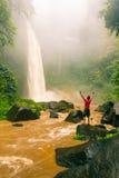 Ο νέος ισχυρός ταξιδιώτης ατόμων απολαμβάνει τη θεαματική θέα πρωινού, όμορφος καταρράκτης Nungnung, Ινδονησία Στοκ Φωτογραφία