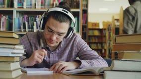 Ο νέος καυκάσιος άνδρας σπουδαστής με τα μεγάλα ακουστικά κάθεται στον πίνακα στη βιβλιοθήκη Πολλά βιβλία είναι γύρω από τον, είν απόθεμα βίντεο