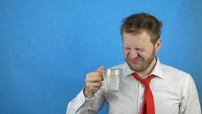 Ο νέος καυκάσιος αρσενικός επιχειρηματίας στον άσπρο δεσμό πουκάμισων και απόλυσης πίνει το νερό με το λεμόνι, υπνηλία, μπλε υπόβ απόθεμα βίντεο