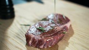 Ο νέος μάγειρας ποτίζει την μπριζόλα βόειου κρέατος με τη σάλτσα στην κουζίνα του φραγμού φιλμ μικρού μήκους