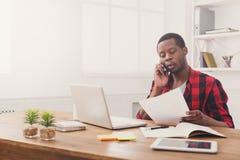 Ο νέος μαύρος επιχειρηματίας διάβασε τα έγγραφα και τη συζήτηση σε κινητό στο σύγχρονο άσπρο γραφείο Στοκ φωτογραφία με δικαίωμα ελεύθερης χρήσης