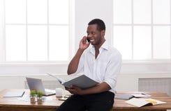 Ο νέος μαύρος επιχειρηματίας διάβασε τα έγγραφα και τη συζήτηση σε κινητό στο σύγχρονο άσπρο γραφείο Στοκ εικόνα με δικαίωμα ελεύθερης χρήσης