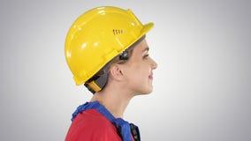 Ο νέος μηχανικός γυναικών με το κίτρινο κράνος ασφάλειας που περπατά και που χαμογελά στο υπόβαθρο κλίσης φιλμ μικρού μήκους