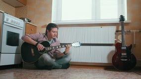 Ο νέος μουσικός παίζει τη συνεδρίαση κιθάρων στο πάτωμα στην κουζίνα απόθεμα βίντεο