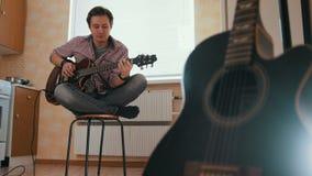 Ο νέος μουσικός τύπων συνθέτει τη μουσική στην κιθάρα και παίζει στην κουζίνα, άλλο μουσικό όργανο στο πρώτο πλάνο, απόθεμα βίντεο