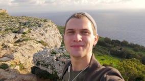 Ο νέος μπλε-eyed τύπος κάνει ένα selfie στο υπόβαθρο της φύσης, θάλασσα, βράχοι Η θυελλώδης ημέρα, ταξίδι, τεχνολογία, ικανοποίησ απόθεμα βίντεο