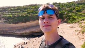 Ο νέος μπλε-eyed τύπος με δύο γυαλιά ηλίου κάνει ένα selfie ενάντια στο σκηνικό της φύσης, ο κόλπος, οι βράχοι με πράσινο φιλμ μικρού μήκους