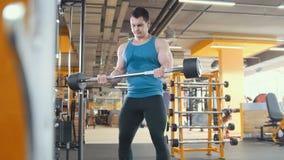Ο νέος μυϊκός αθλητής αυξάνει το φραγμό στο δωμάτιο workout Στοκ εικόνες με δικαίωμα ελεύθερης χρήσης