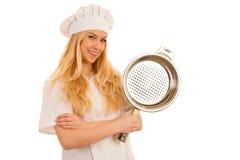Ο νέος ξανθός αρχιμάγειρας woamn κρατά το σκεύος για την κουζίνα όπως προετοιμάζεται στο γουργούρισμα Στοκ Εικόνα