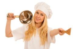 Ο νέος ξανθός αρχιμάγειρας woamn κρατά το σκεύος για την κουζίνα όπως προετοιμάζεται στο γουργούρισμα Στοκ Φωτογραφίες