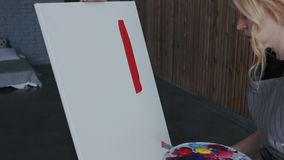 Ο νέος ξανθός θηλυκός καλλιτέχνης στην ποδιά παίρνει το κόκκινο χρώμα από την παλέτα και κάνει την πρώτη κηλίδα με spatula επάνω απεικόνιση αποθεμάτων