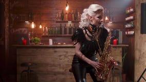 Ο νέος ξανθός θηλυκός μουσικός εκτελεί ένα τραγούδι στη συνεδρίαση saxophone της σε μια υψηλή καρέκλα φραγμών φιλμ μικρού μήκους