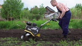 Ο νέος ξανθός μυϊκός αγρότης καλλιεργεί το επίγειο χώμα με το περιστροφικό μίνι πηδάλιο φιλμ μικρού μήκους
