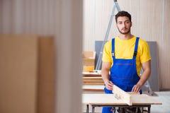 Ο νέος ξυλουργός επισκευαστών που απασχολείται στο τέμνον ξύλο Στοκ Εικόνες