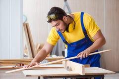 Ο νέος ξυλουργός επισκευαστών που απασχολείται στο τέμνον ξύλο στο κυκλικό πριόνι Στοκ Εικόνες