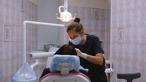Ο νέος οδοντίατρος γυναικών μεταχειρίζεται τα υπομονετικά δόντια ` s Με την παραλαβή στο γιατρό του stomatologist φιλμ μικρού μήκους