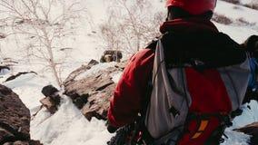 Ο νέος ορειβάτης σε ένα κόκκινο σακάκι, ένα κράνος και ειδικά γυαλιά στέκεται σε μια βουνοπλαγιά και μοιάζει με το χιονισμένο φιλμ μικρού μήκους