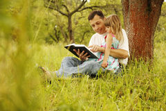 Ο νέος πατέρας με τη μικρή κόρη του διαβάζει τη Βίβλο στοκ εικόνα