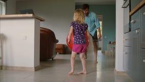 Ο νέος πατέρας παίζει την καλαθοσφαίριση με τη μικρή κόρη του με ένα μεγάλο κόκκινο μπαλόνι γυμναστικής στο καθιστικό κίνηση αργή απόθεμα βίντεο