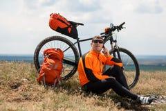 Ο νέος ποδηλάτης στο πορτοκαλί πουκάμισο ελέγχει το τηλέφωνό του Στοκ εικόνα με δικαίωμα ελεύθερης χρήσης