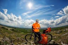 Ο νέος ποδηλάτης στο πορτοκαλί πουκάμισο ελέγχει το τηλέφωνό του Στοκ φωτογραφίες με δικαίωμα ελεύθερης χρήσης