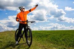 Ο νέος ποδηλάτης στο πορτοκαλί πουκάμισο ελέγχει το τηλέφωνό του Στοκ Εικόνες