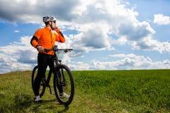 Ο νέος ποδηλάτης στο πορτοκαλί πουκάμισο ελέγχει το τηλέφωνό του Στοκ φωτογραφία με δικαίωμα ελεύθερης χρήσης