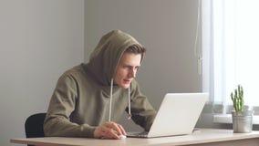 Ο νέος προγραμματιστής που εργάζεται σε ένα lap-top, κάνει μια χειρονομία νίκης μετά από μια επιτυχή συναλλαγή απόθεμα βίντεο