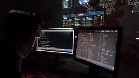 Ο νέος προγραμματιστής ΤΠ τυπώνει τον κώδικα στον υπολογιστή στο σκοτεινό δωμάτιο γραφείων φιλμ μικρού μήκους
