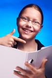 Ο νέος σπουδαστής eyeglasses παρουσιάζει στο φάκελλο με το δάχτυλο Στοκ Εικόνες