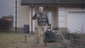 Ο νέος στρατιώτης στους στρατιωτικούς περίβολους με τη μεγάλη τσάντα που στέκεται μπροστά από το σπίτι Ένα άτομο που πηγαίνει στη φιλμ μικρού μήκους