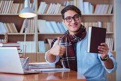 Ο νέος συγγραφέας βιβλίων που γράφει στη βιβλιοθήκη Στοκ εικόνες με δικαίωμα ελεύθερης χρήσης