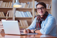 Ο νέος συγγραφέας βιβλίων που γράφει στη βιβλιοθήκη Στοκ Εικόνες