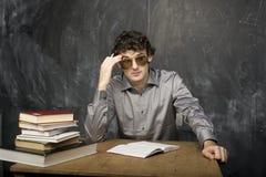 Ο νέος συναισθηματικός σπουδαστής με τα βιβλία και κόκκινο μήλο στο δωμάτιο κατηγορίας Στοκ Εικόνα